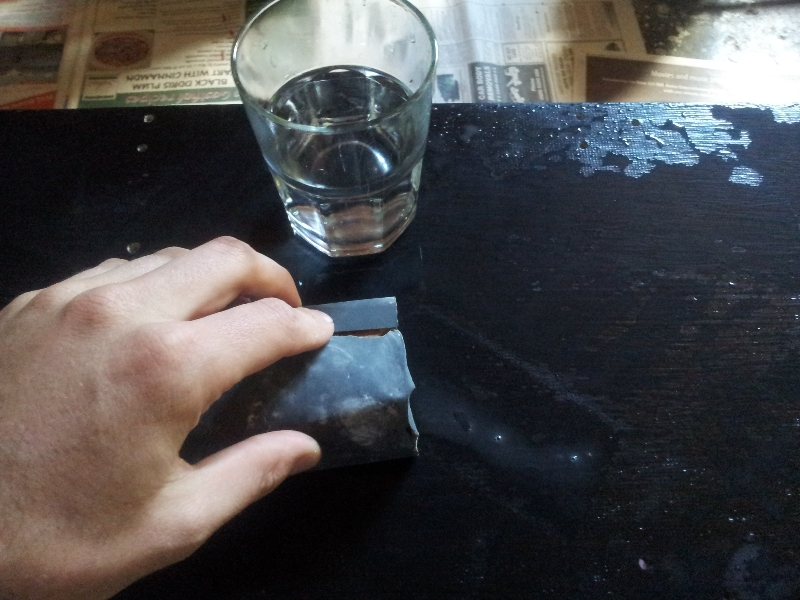 Sanding the bottom of the board with wet-and-dry.