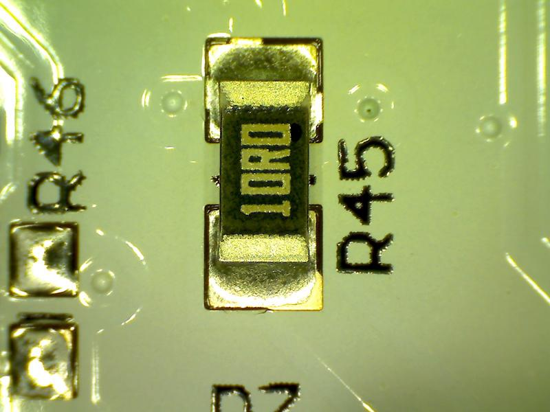 A close-up of a 0603 resistor and it's designator on a PCB.
