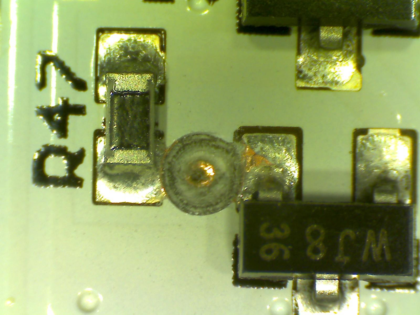 A drilled-out via (to break the connection) between a 0603 resistor and SOT-23-3 MOSFET.