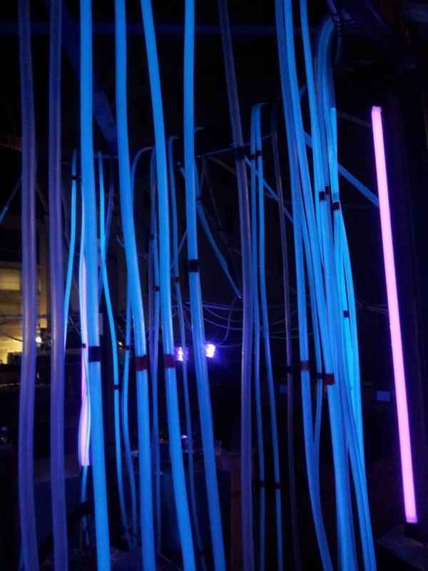 The central structure and the tonic-filled pipes glowing under UV light.